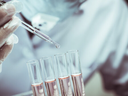 Scientist,Dropping,Chemical,Liquid,To,Flask,With,Lab,Glassware,Background,